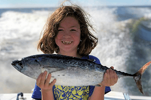 Check the great smile on this kid with a false albacore tuna on an Outer Banks Fishing Charter.